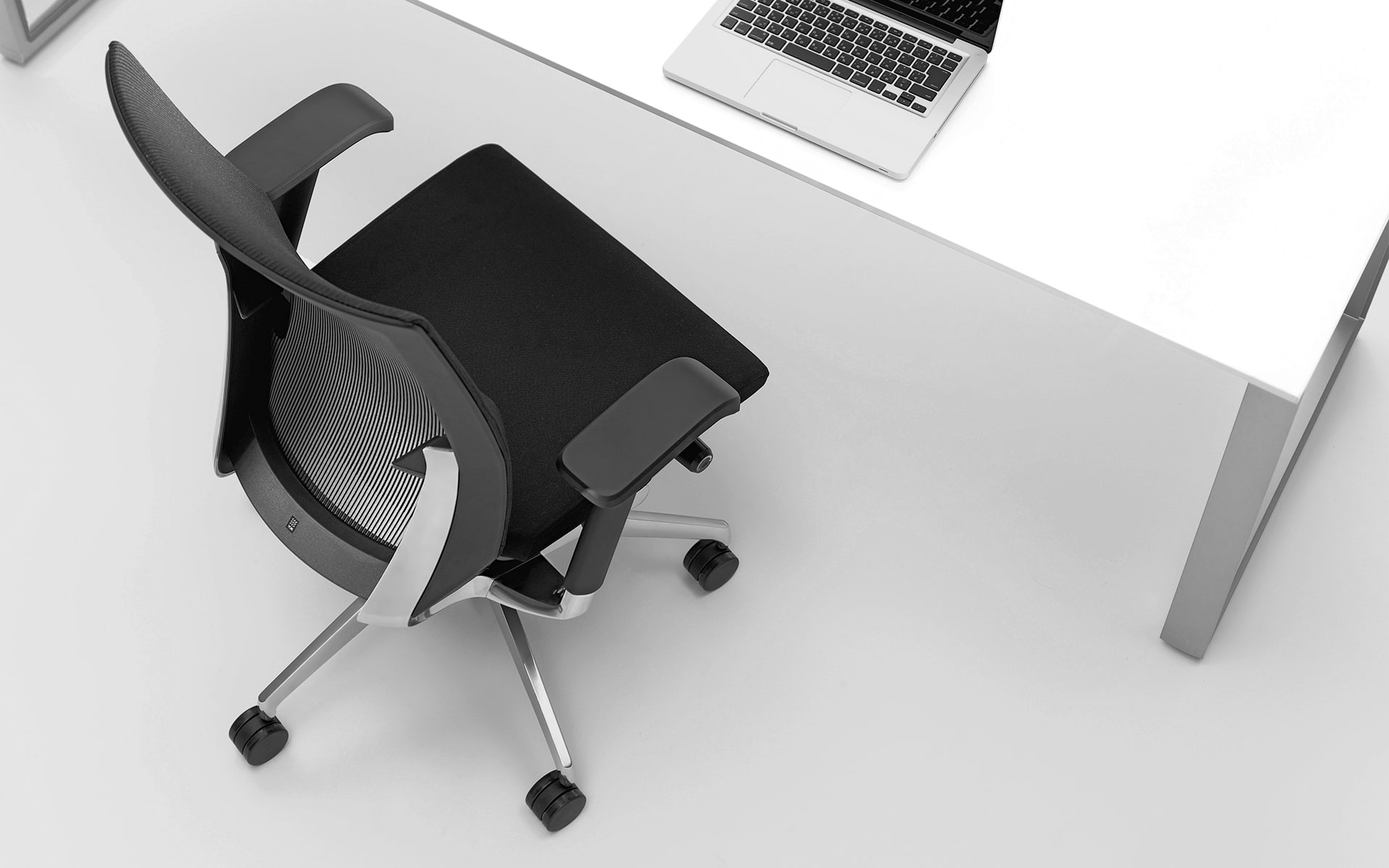 High-angle shot of the ITOKI Vento office chair by ITO Design in black at minimalist desk