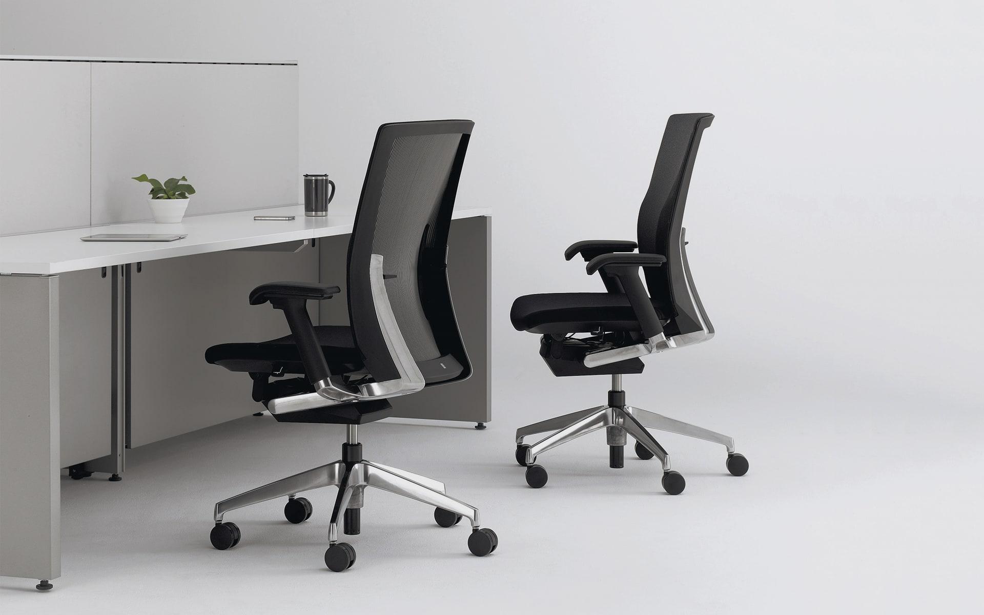 Zwei ITOKI Vento Bürostühle von ITO Design in Schwarz an puristischem Arbeitsplatz