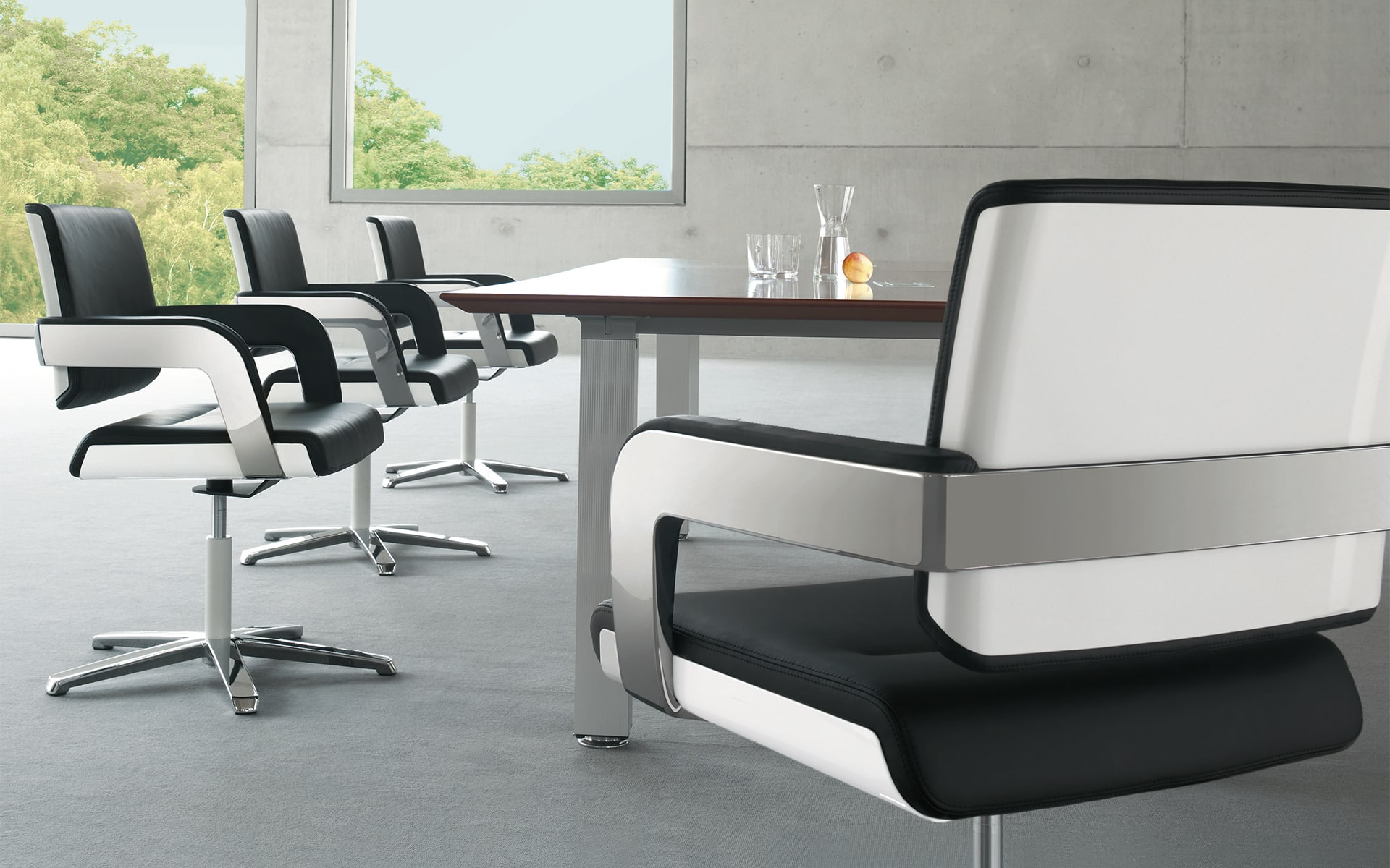 Black-and-white K+N Charta conference chairs by ITO Design in conference hall with large windows