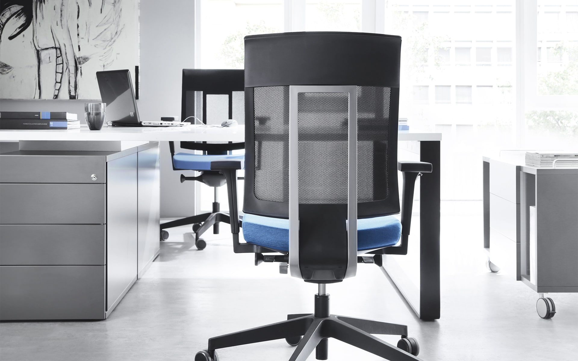 Profim Xenon office chairs by ITO Design with mesh backrests and blue upholstery at modern desk