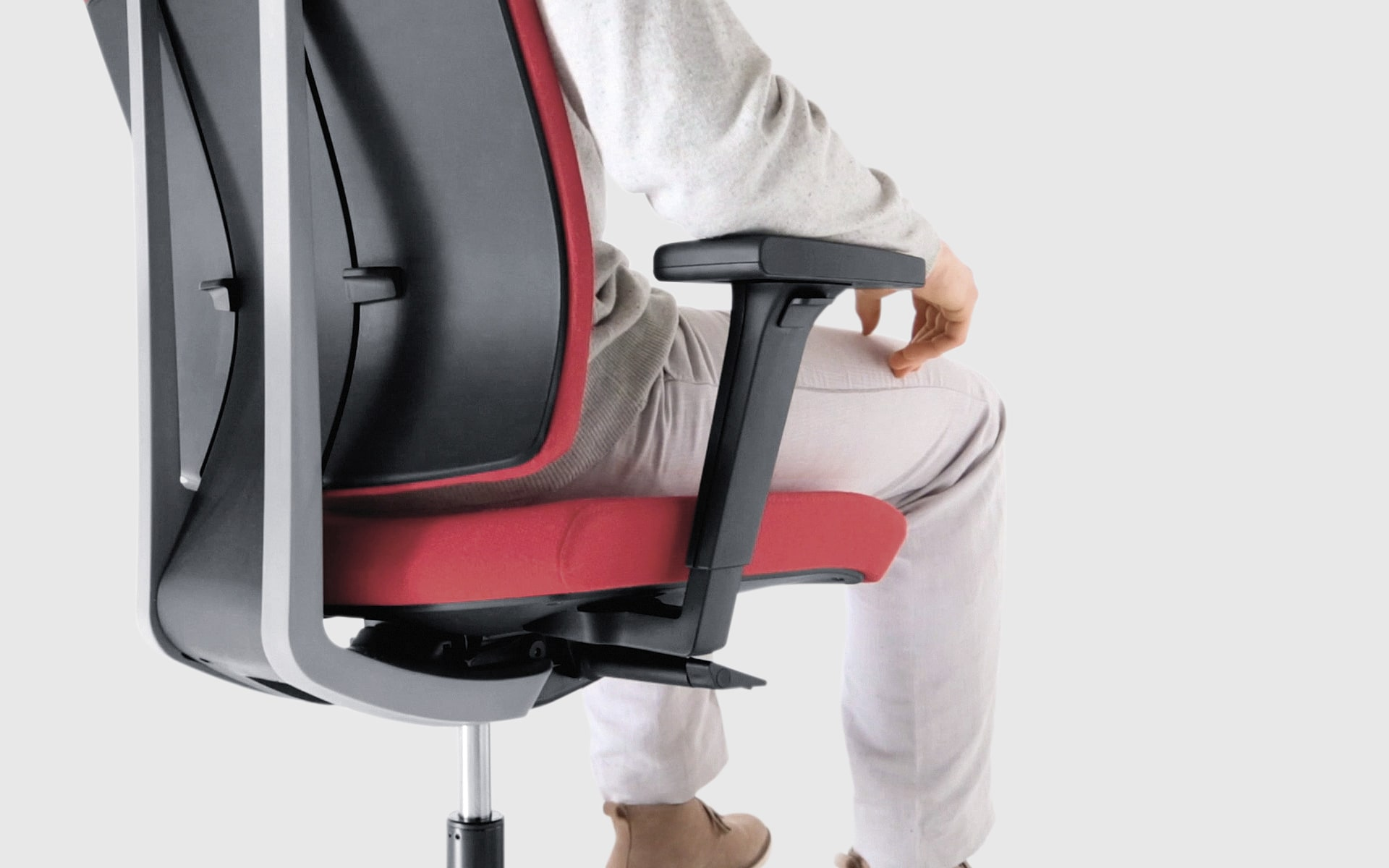 Person sits on Profim Xenon office chair by ITO Design with red upholstery