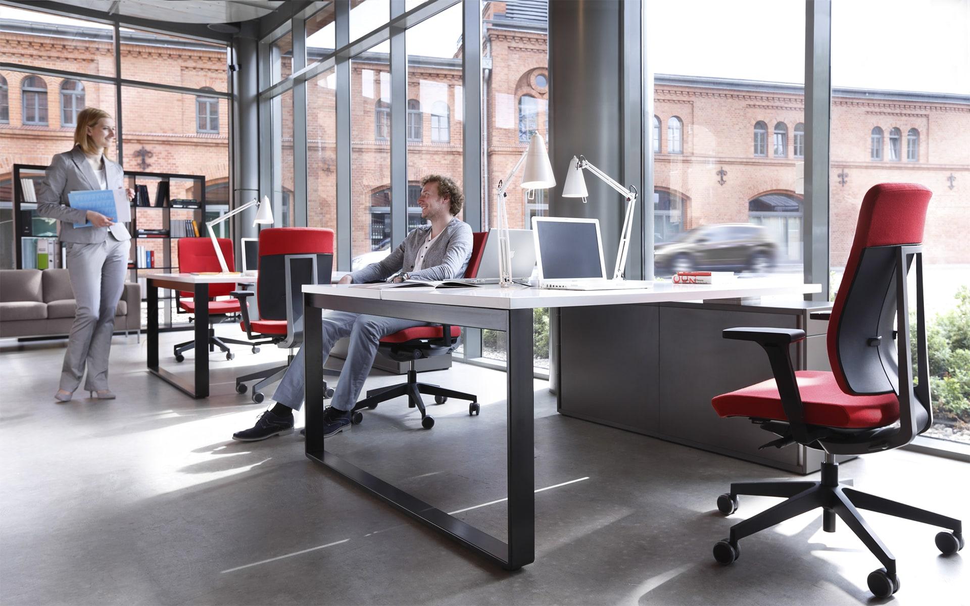Mann und Frau an hellem Arbeitsplatz, der mit roten Profim Xenon Bürostühlen von ITO Design ausgestattet ist