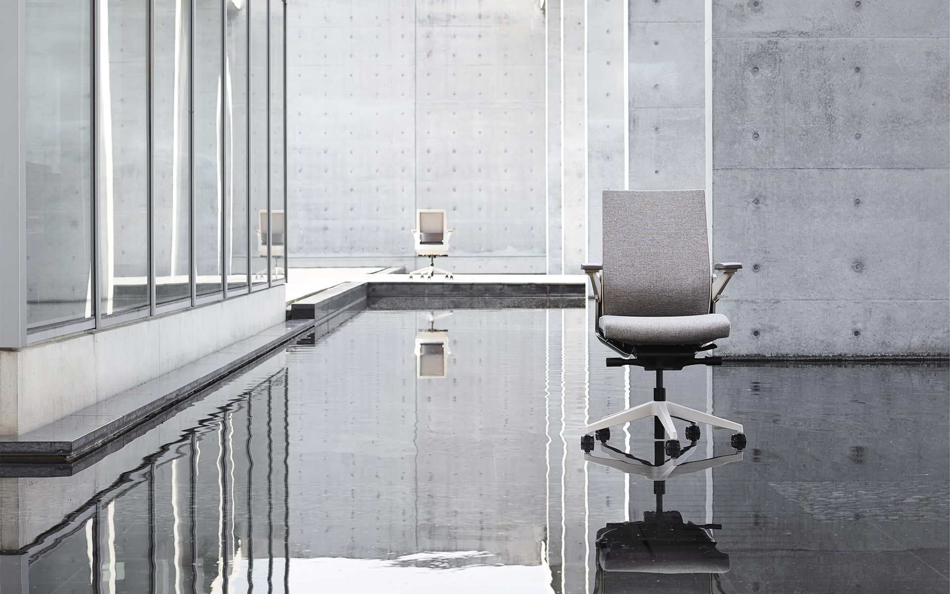 Gray Sidiz T80 executive office chairs by ITO Design on water surface in minimalist outdoor area