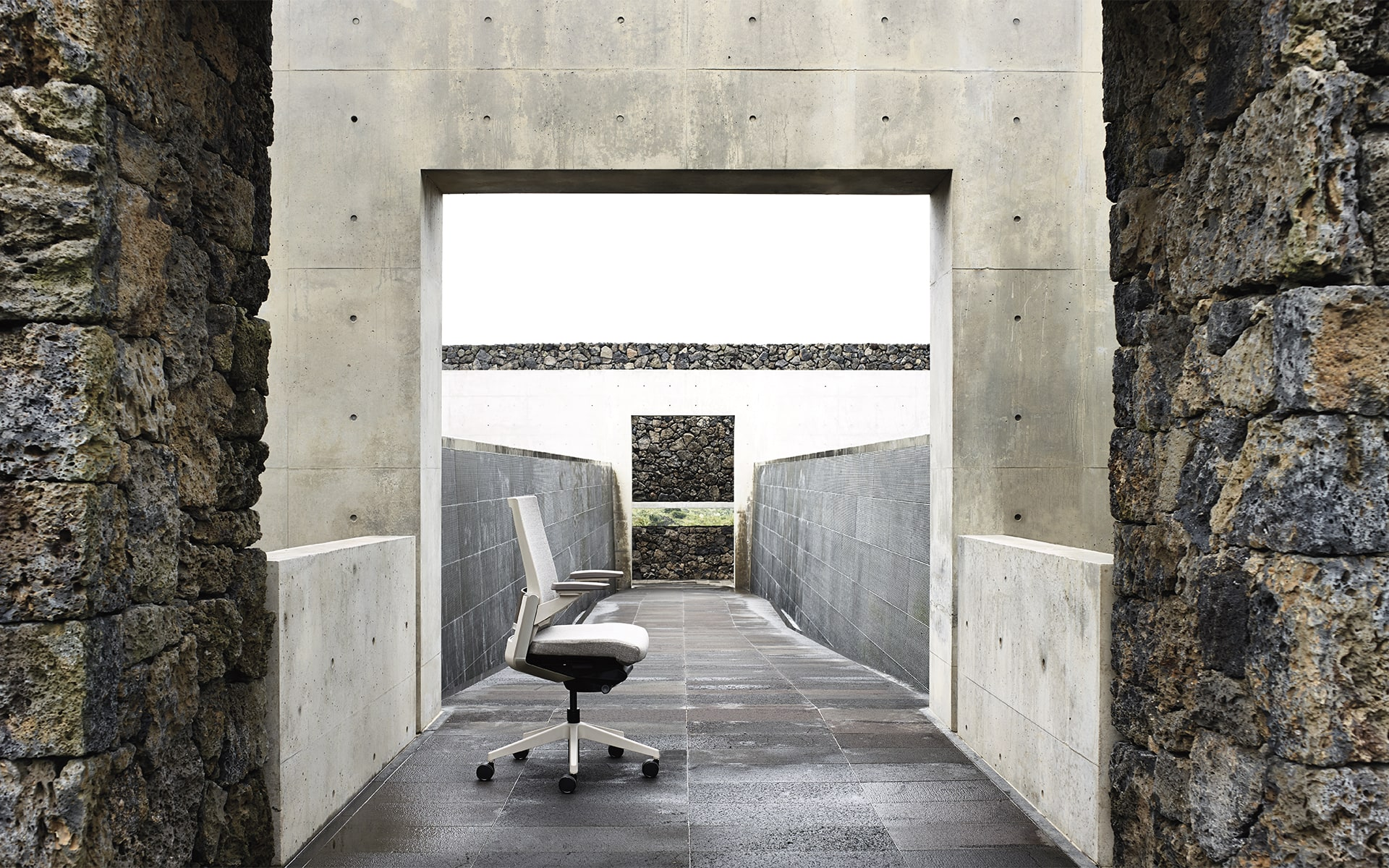 Gray Sidiz T80 executive office chair by ITO Design in outdoor area with raw stones