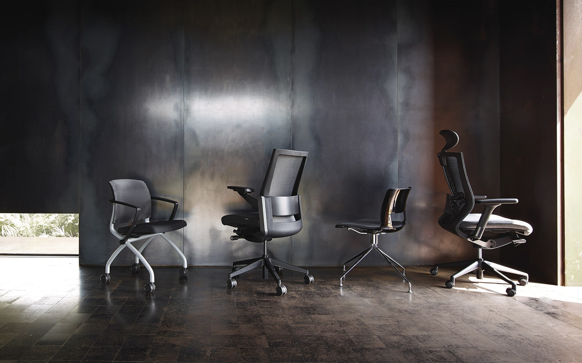 Schwarz-grauer Sidiz T80 Chefsessel von ITO Design mit anderen Stühlen vor Metallwand in leerem Raum