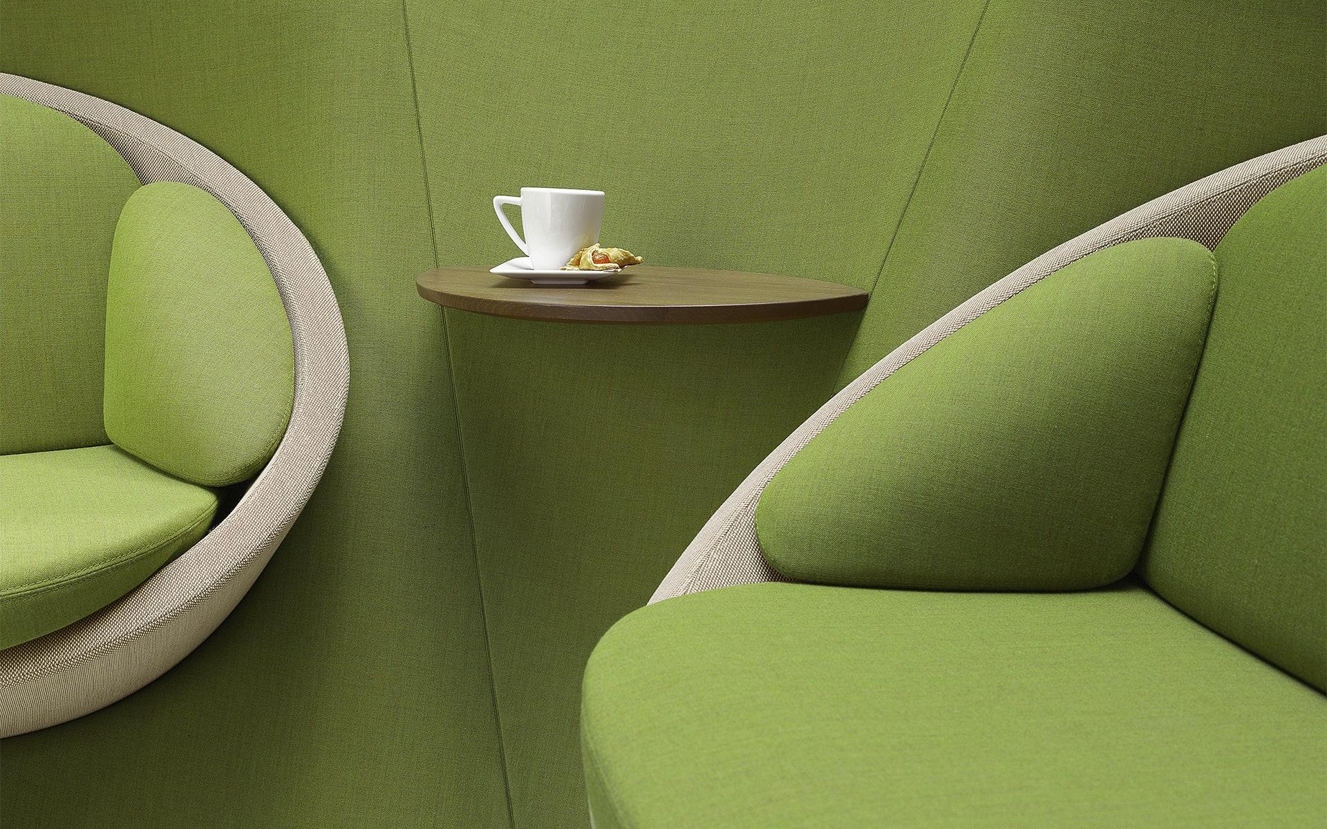 Nahaufnahme des Profim Wyspa Lounge Sitzsystems von ITO Design in grün mit integrierter Ablage