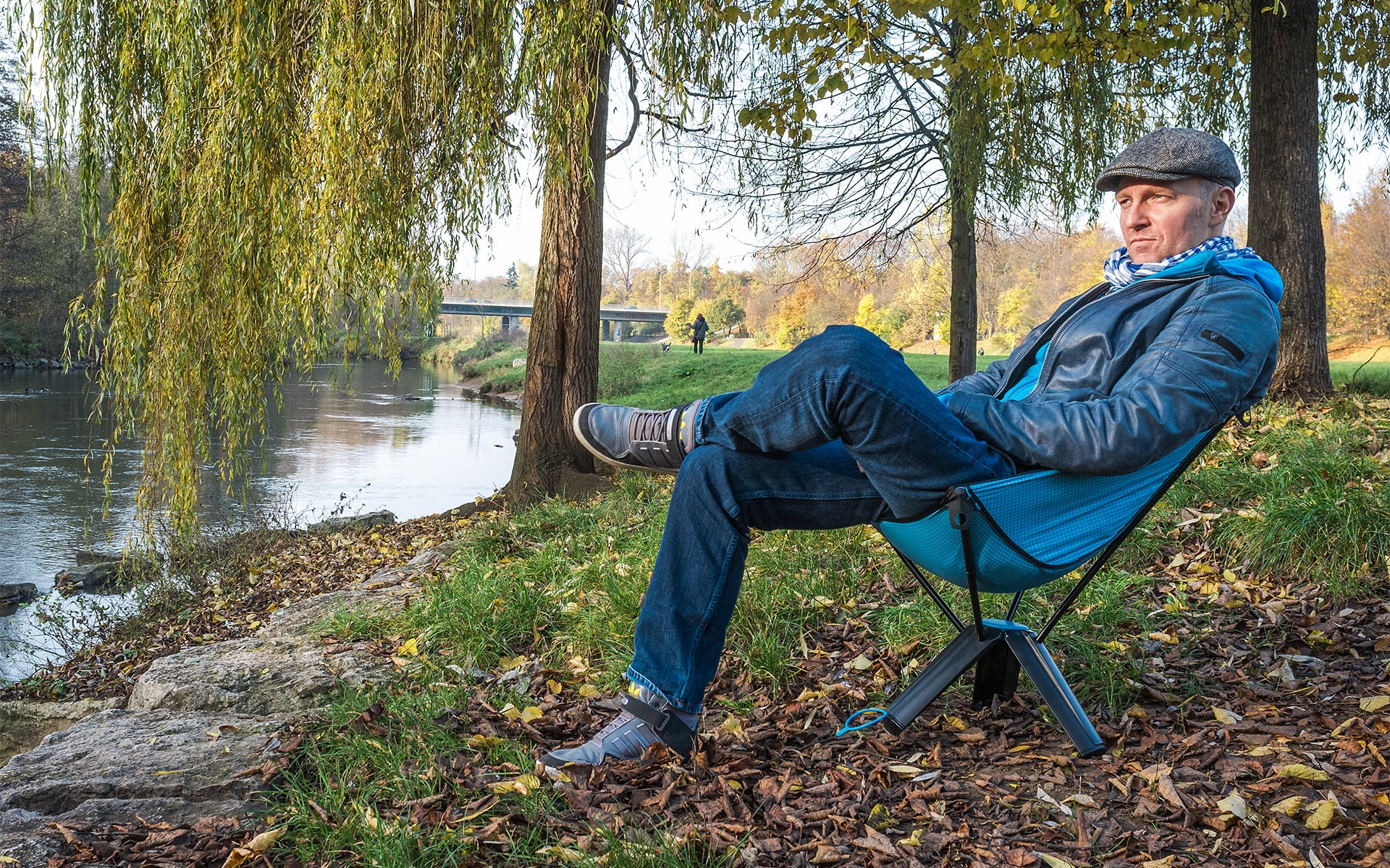 Man sits in collapsable outdoor chair Therm-a-Rest Treo by ITO Design at a riverbank