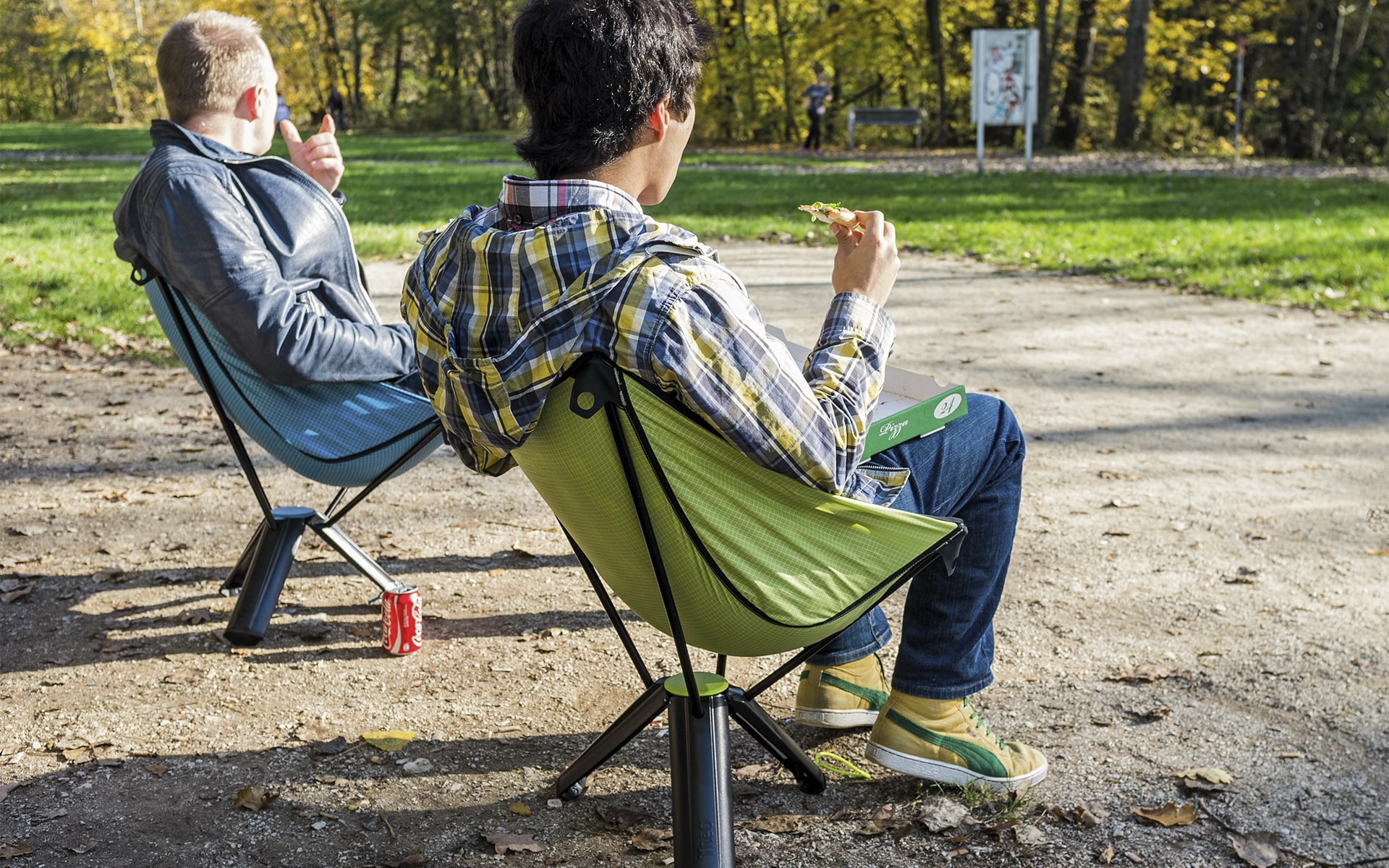 Men sit in park on collapsable outdoor chairs Therm-a-Rest Treo by ITO Design in blue and green