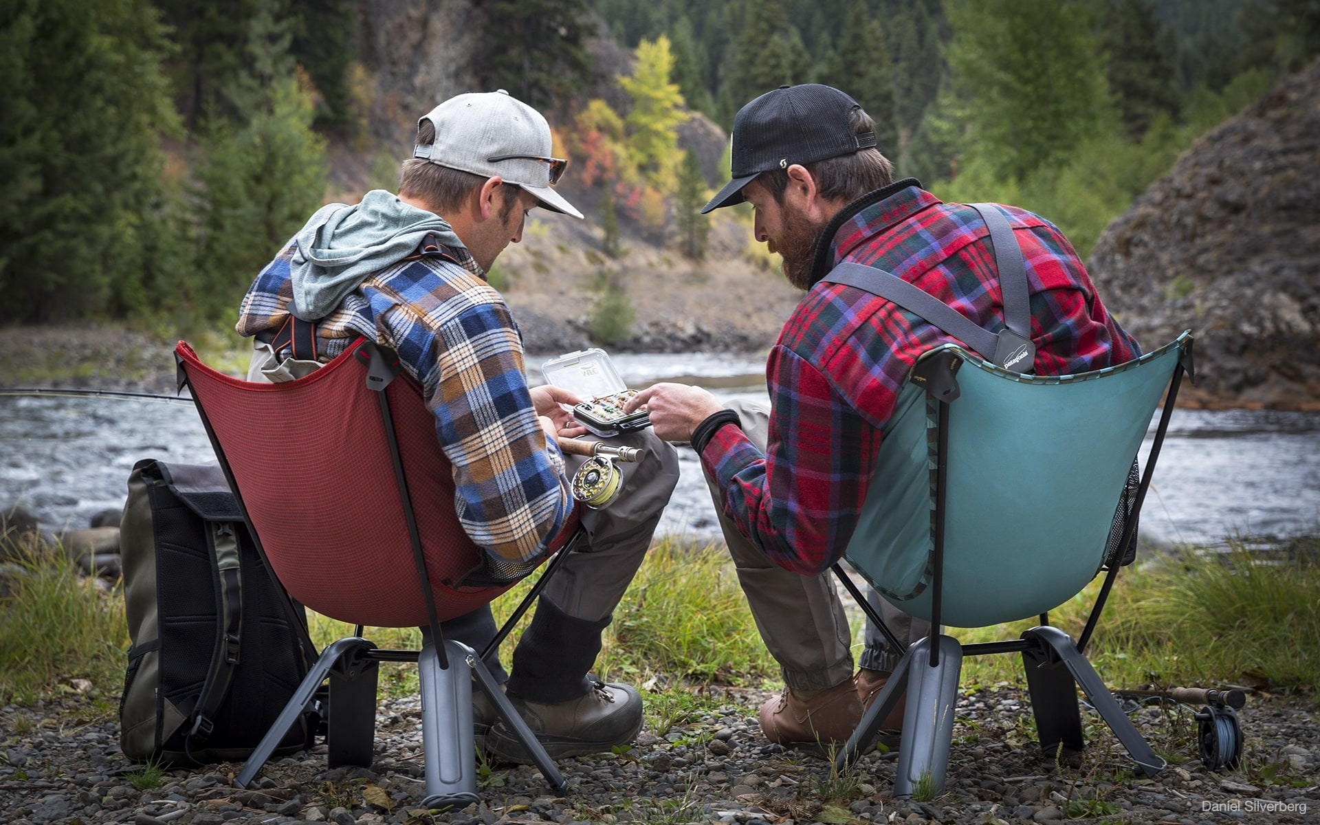 Two men in outdoor outfits sitting in red and green Therm-a-Rest Quadra camp chairs by ITO Design near river, looking at fishing baits