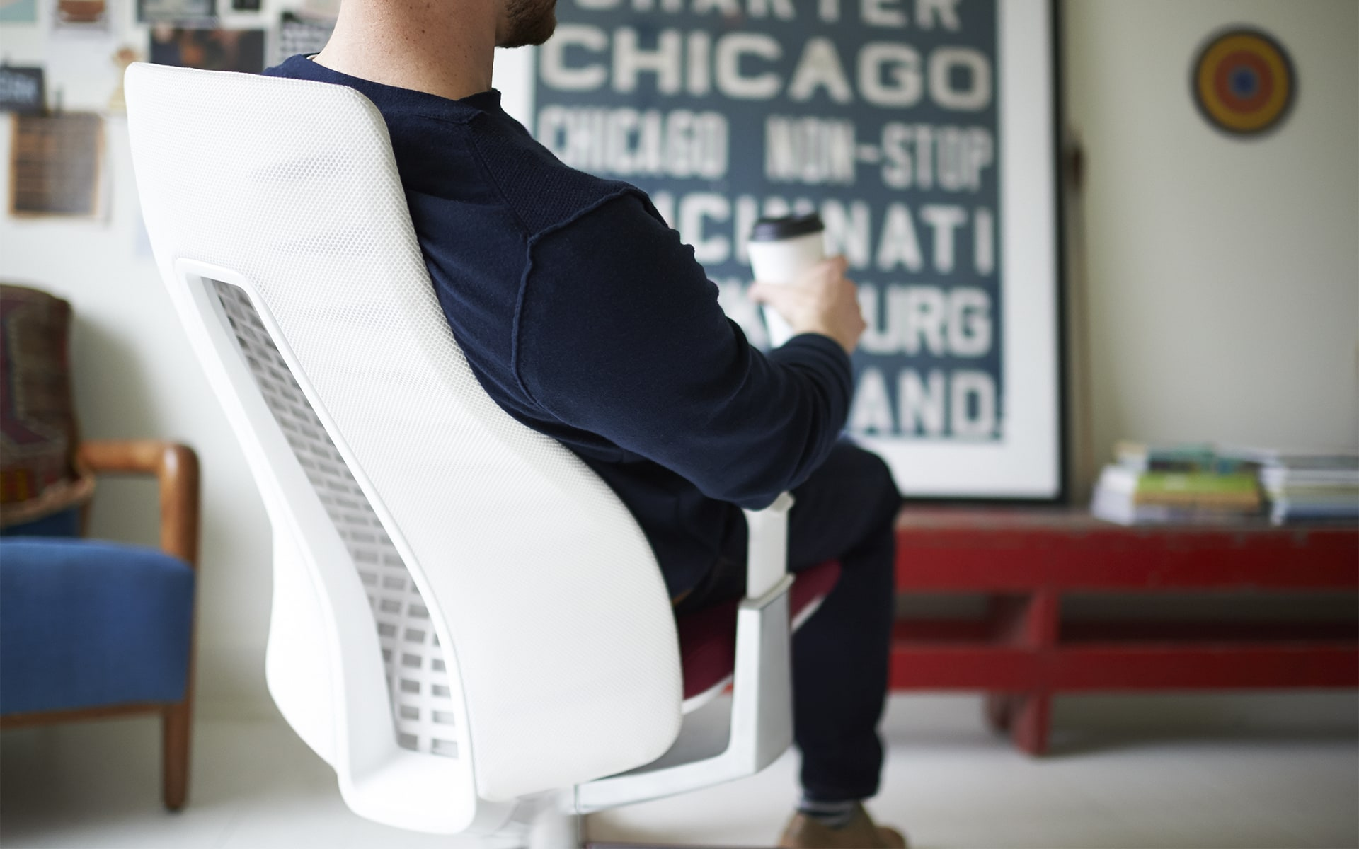 Man with coffee to go sits on Haworth Fern office chair by ITO Design with white backrest