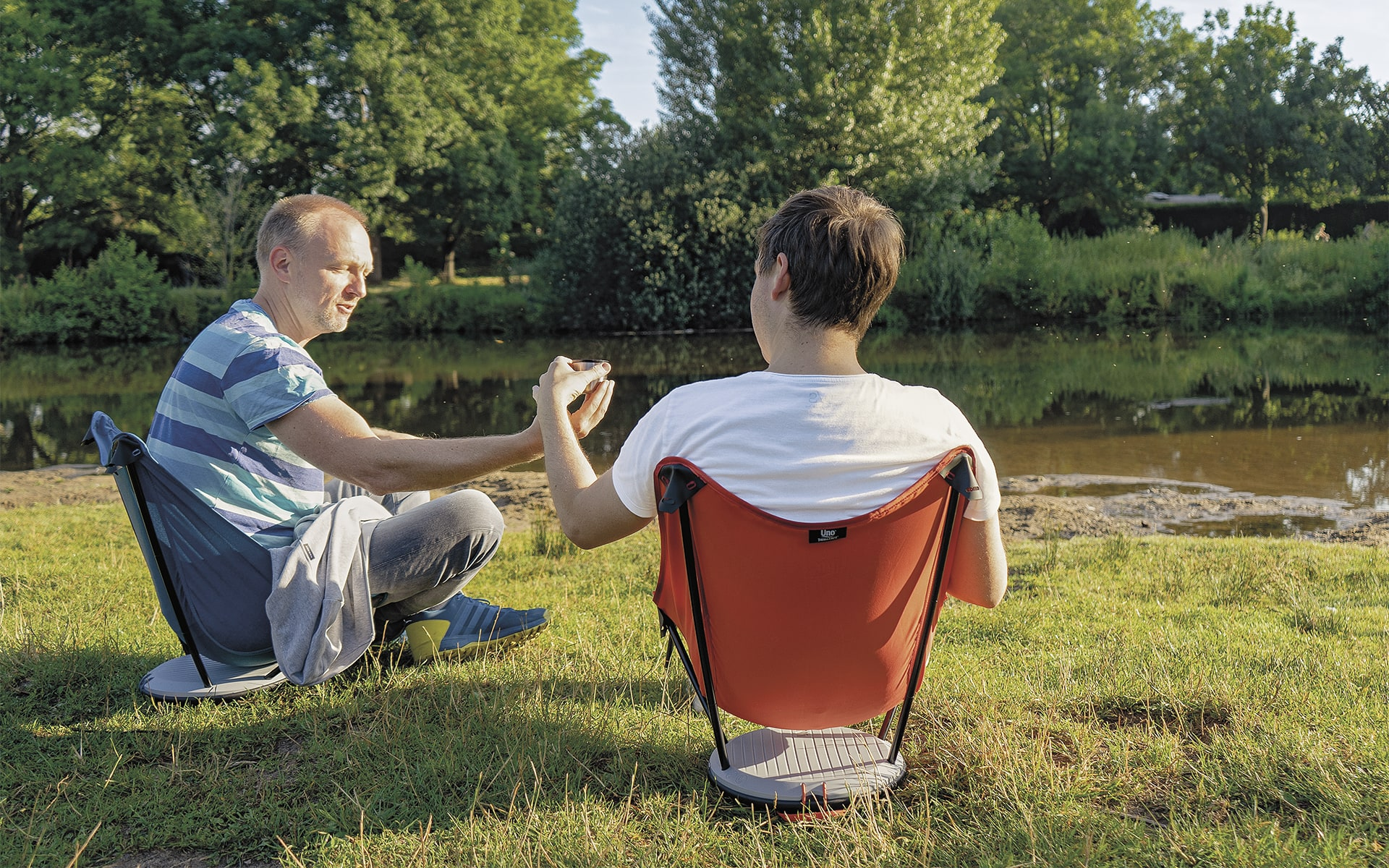 Two men in leisure clothing sitting in blue and red Therm-a-Rest Uno outdoor chairs by ITO Design near river, one handing the other a cup