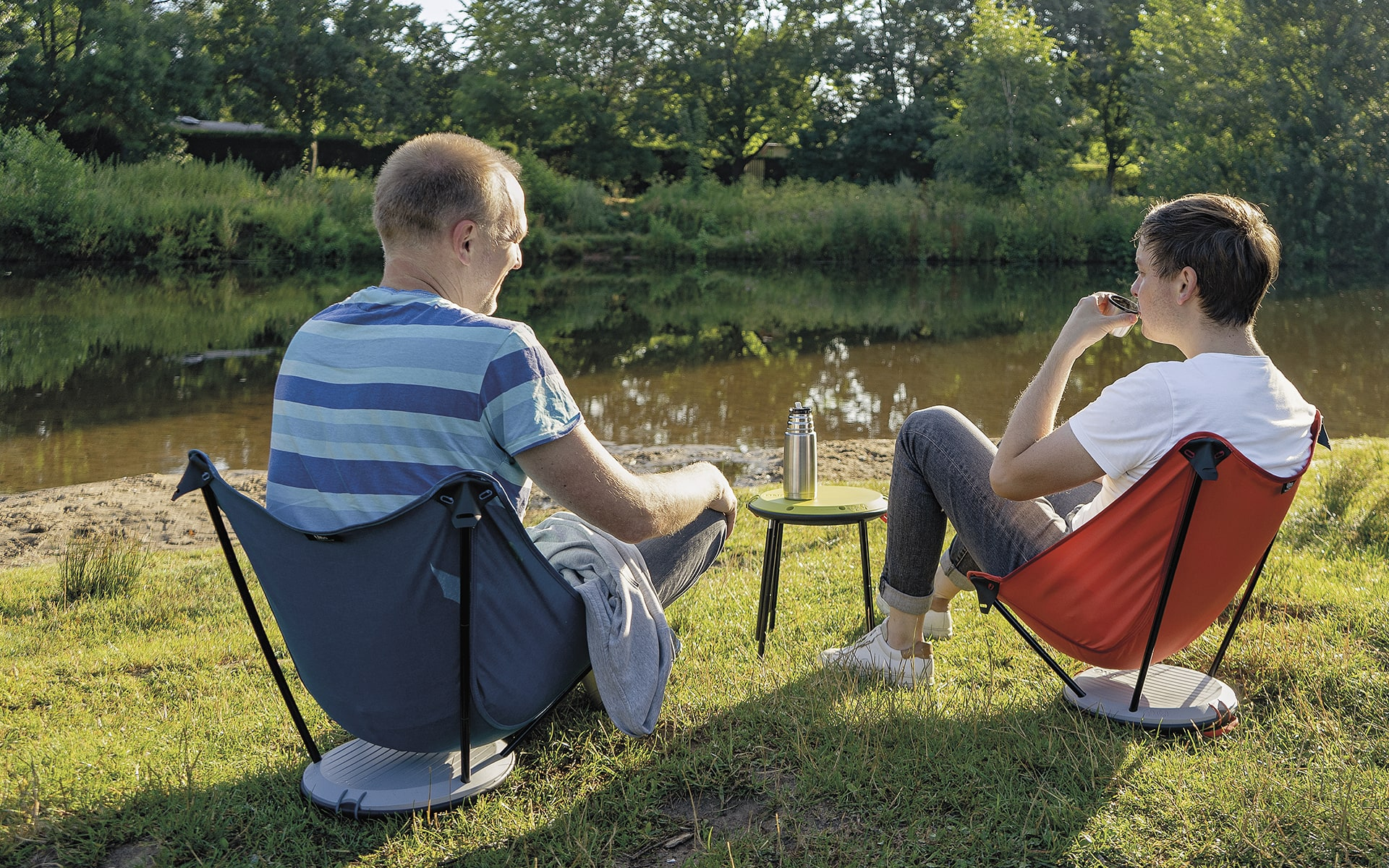 Two men sitting in blue and red Therm-a-Rest Uno outdoor chairs by ITO Design near river, using a collapsed Therm-a-Rest Uno outdoor chair as a side table