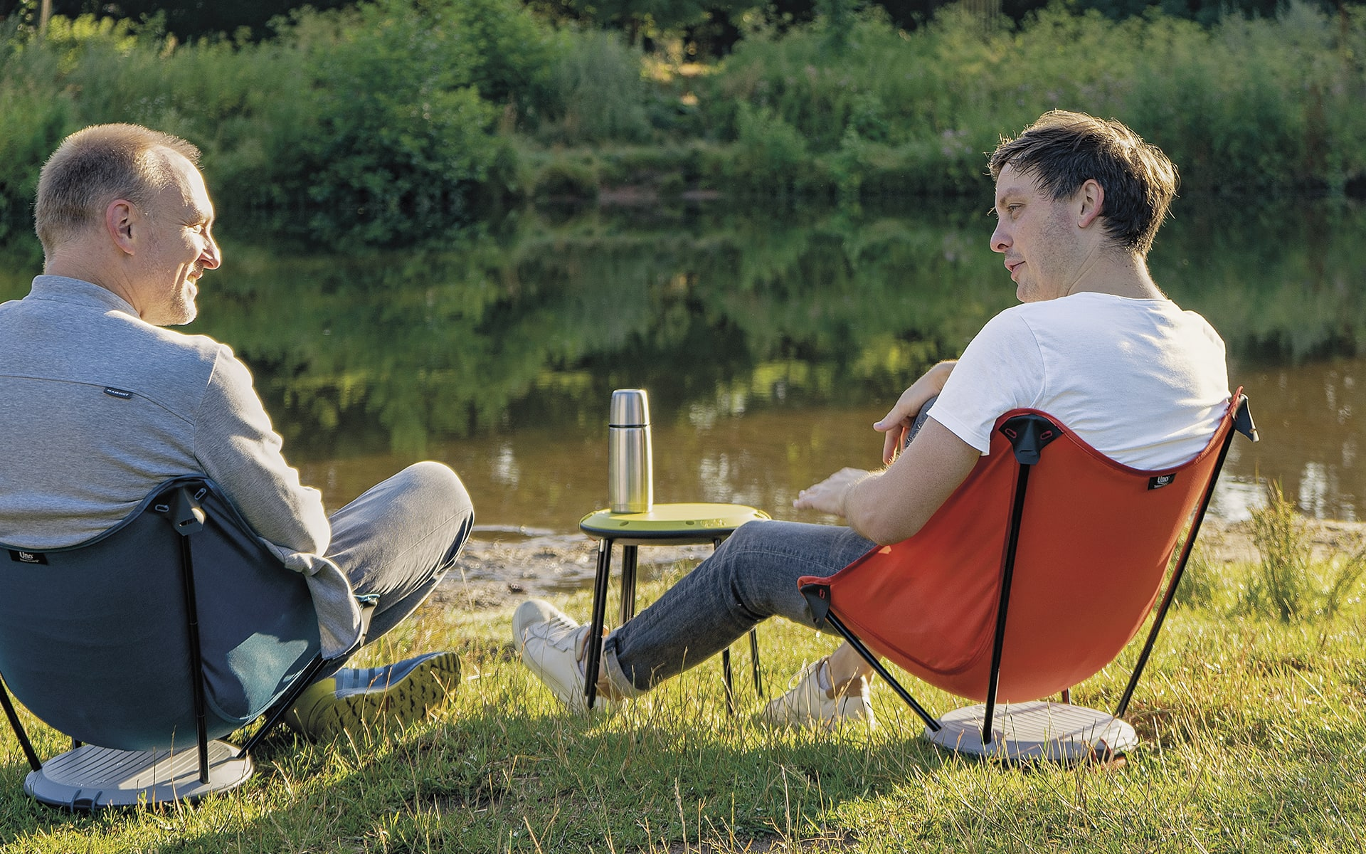 Two men sitting in Therm-a-Rest Uno outdoor chairs by ITO Design near river, using a collapsed Therm-a-Rest Uno outdoor chair as a side table and talking to each other