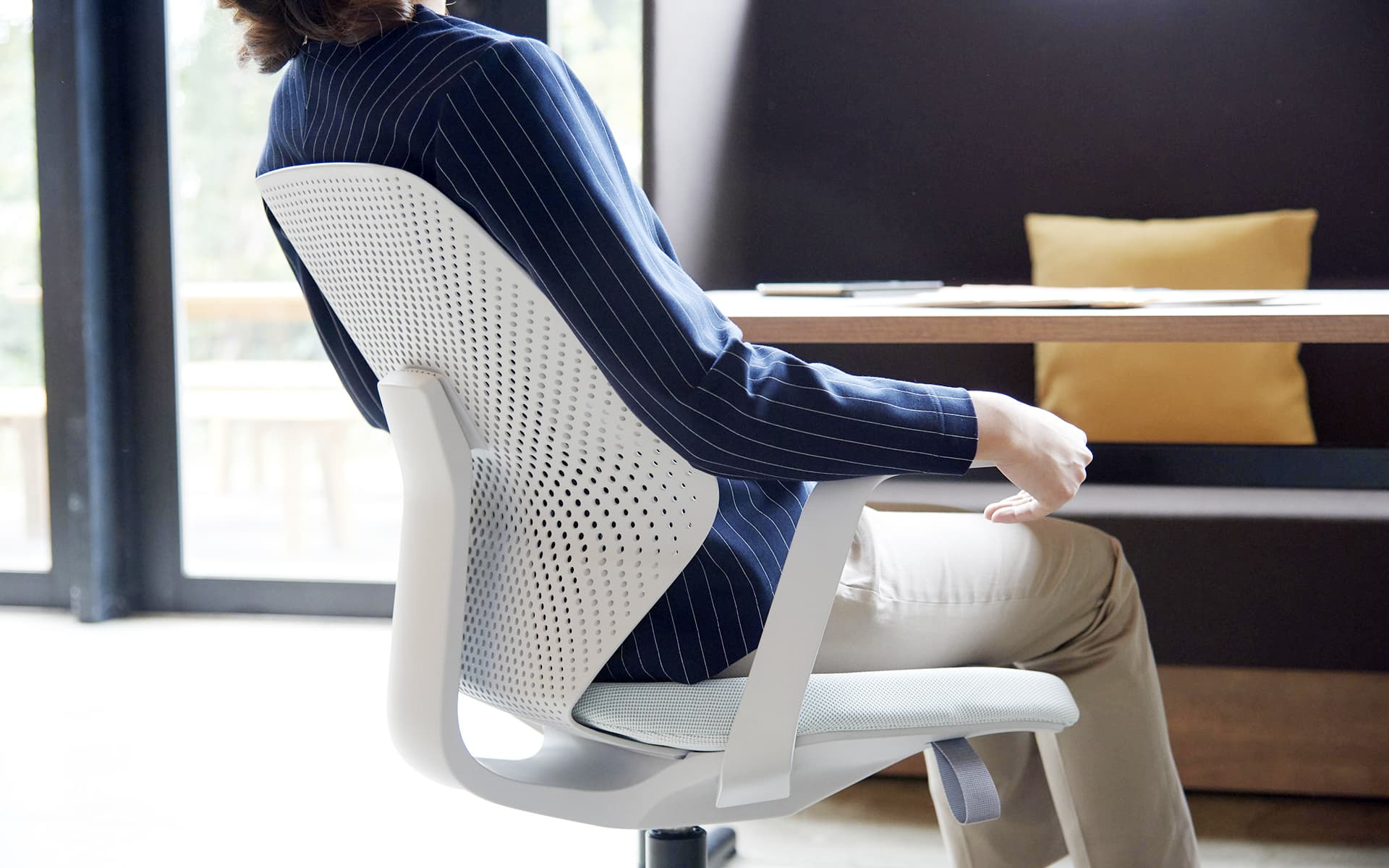 An elegantly dressed woman sits in a white ITOKI QuA office chair by ITO Design