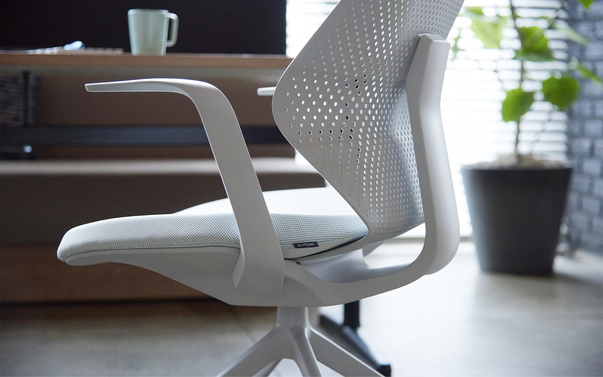 A white ITOKI QuA office chair by ITO Design in front of a natural wood desk with mug