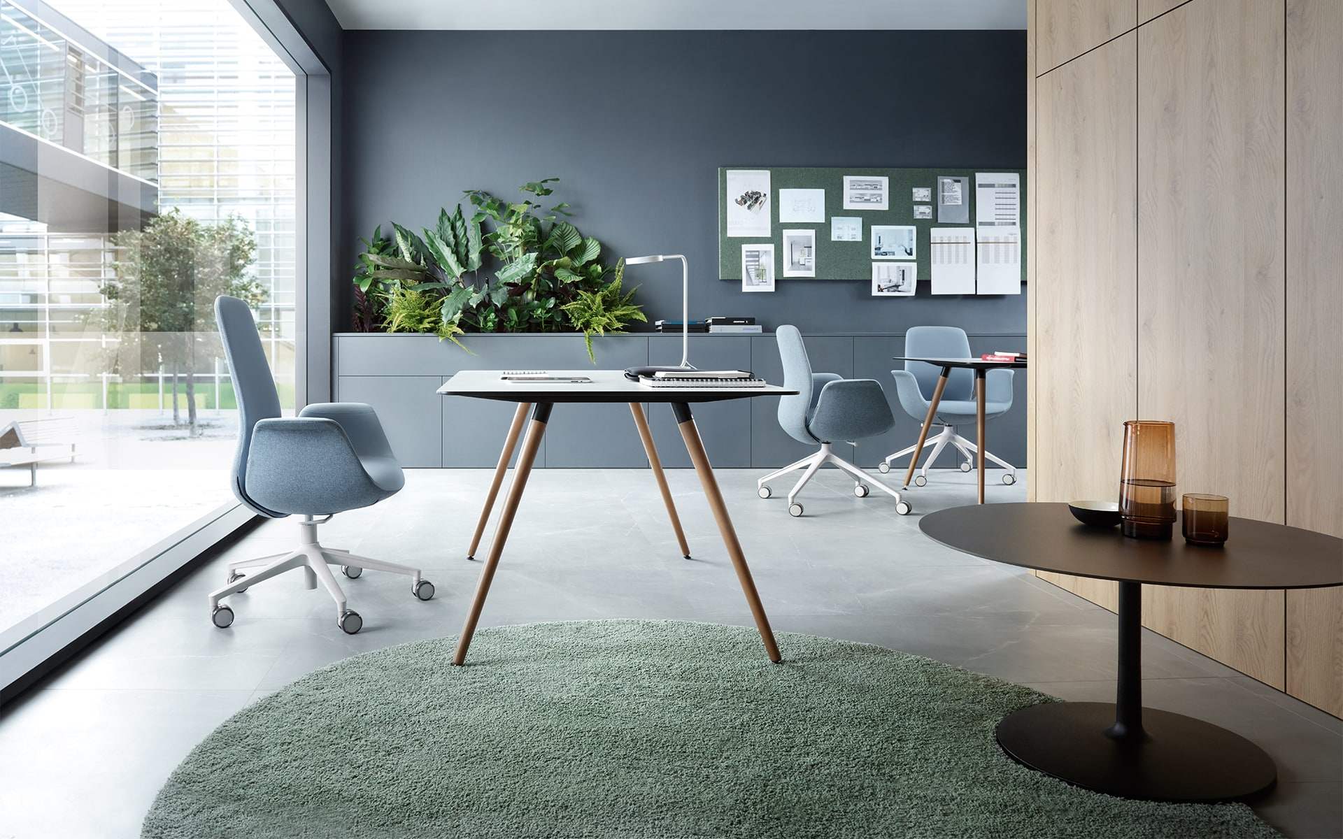 Three blue grey Profim Ellie chairs by ITO Design in light-flooded modern office