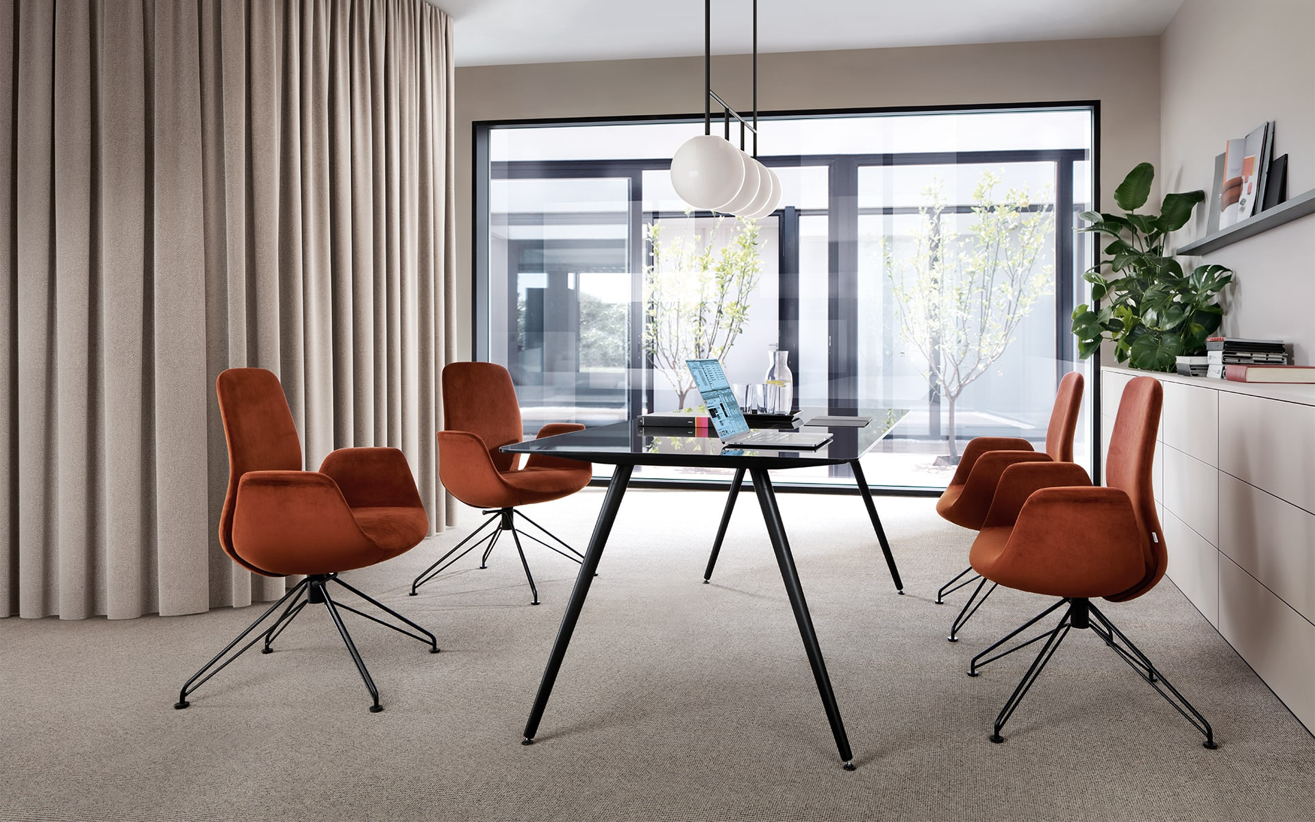 Four rust-red Profim Ellie chairs with black metal legs by ITO Design in modern conference room