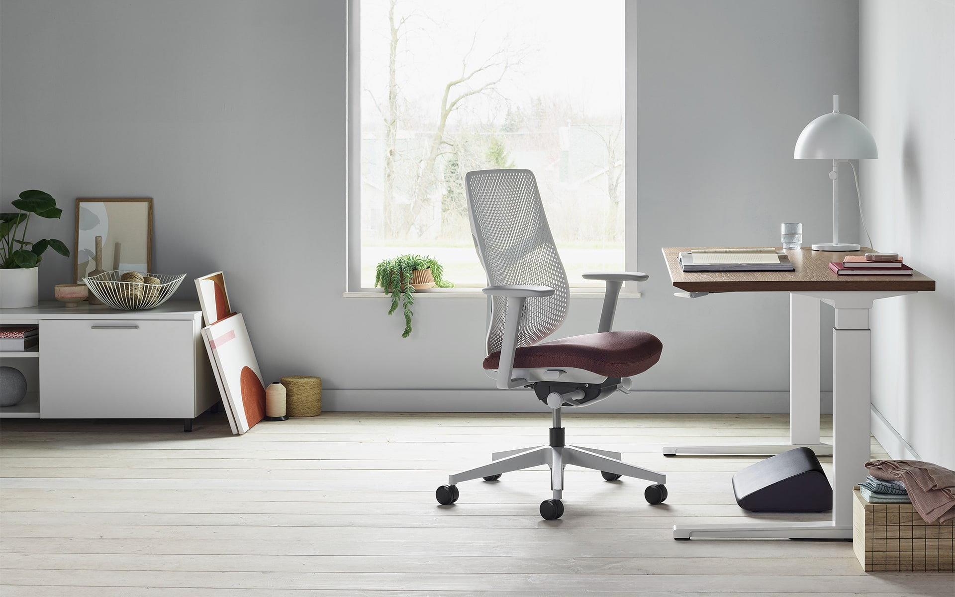 A Hermann Miller Verus office chair by ITO Design with light grey perforated backrest and berry-colored seat cushion in modern home office