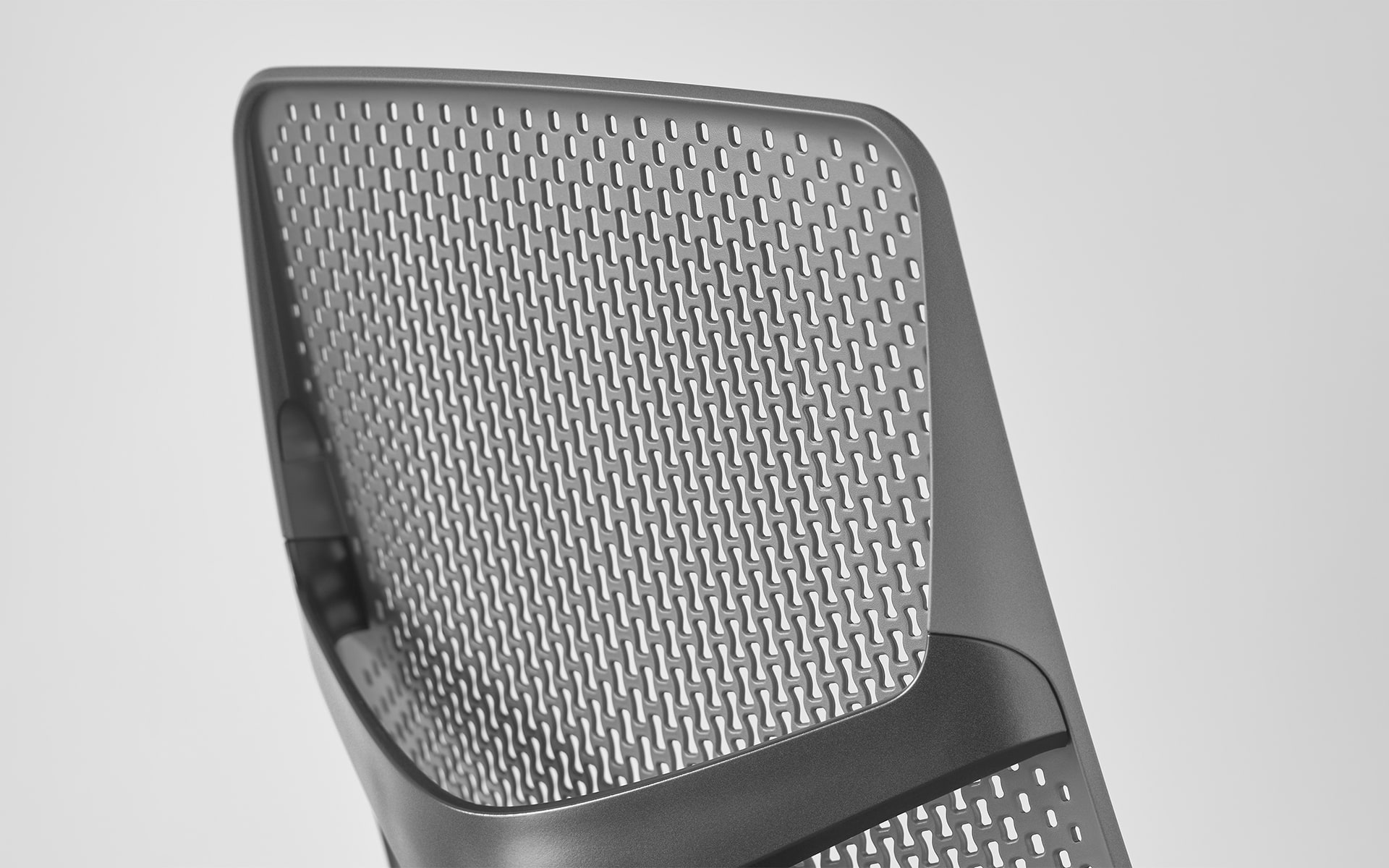 Close-up of the ergonomic perforated plastic backrest of a Hermann Miller Verus office chair by ITO Design