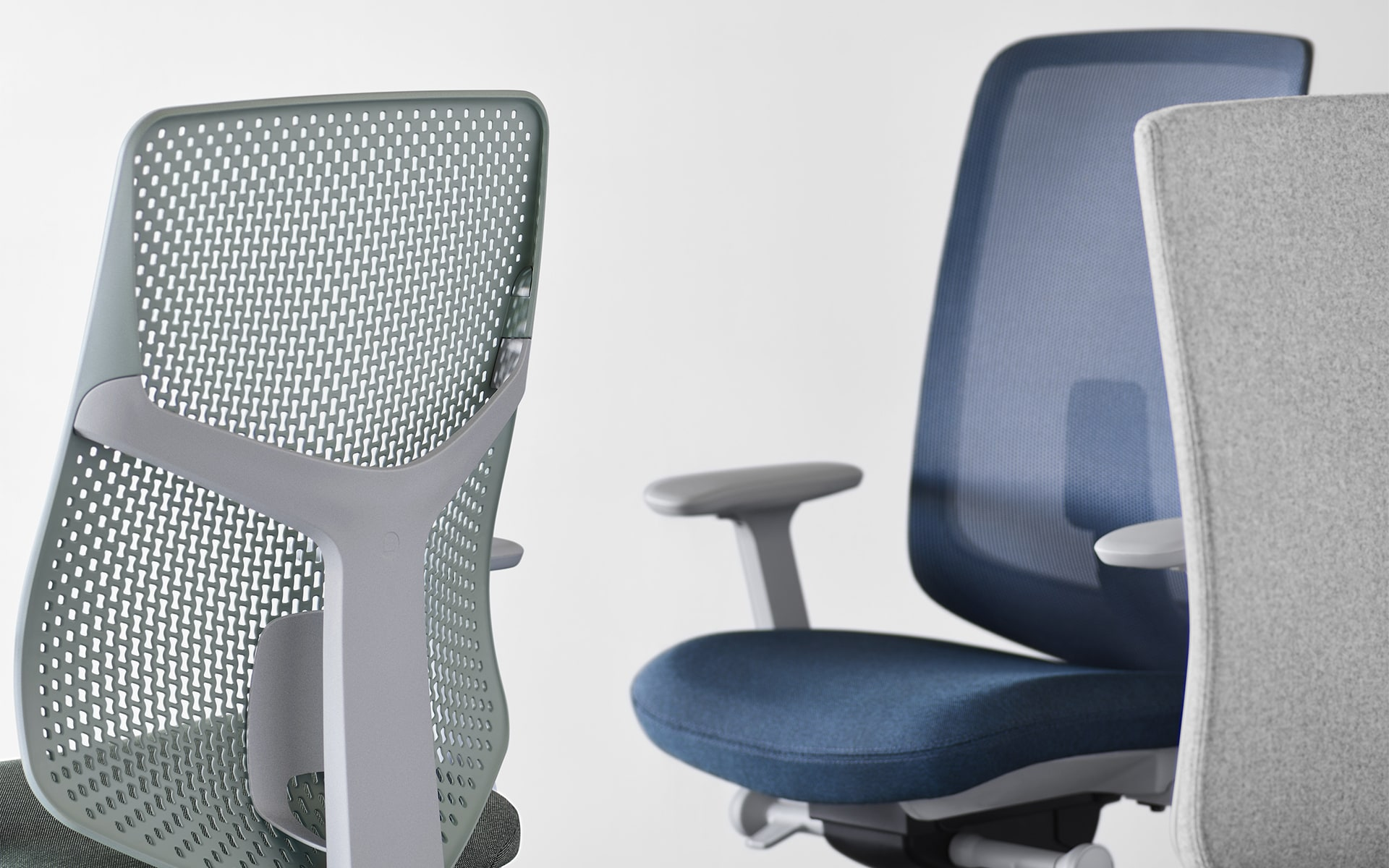 Close-ups of three chairs of the Hermann Miller Verus office chair family by ITO Design - one with the new perforated plastic backrest and two with other backrests