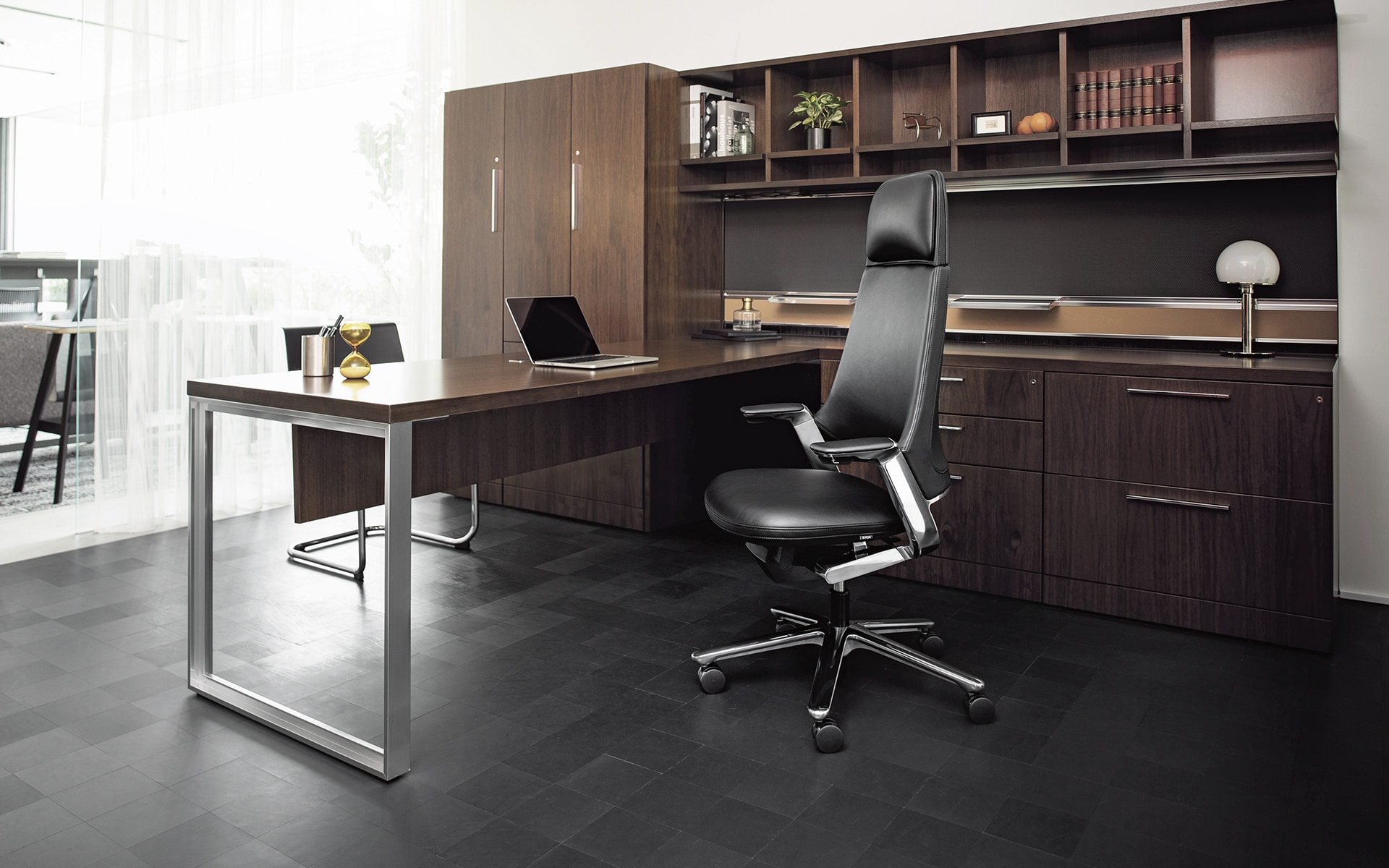 The ITOKI Leonis executive chair by ITO Design in black in an elegant office with dark wood furniture