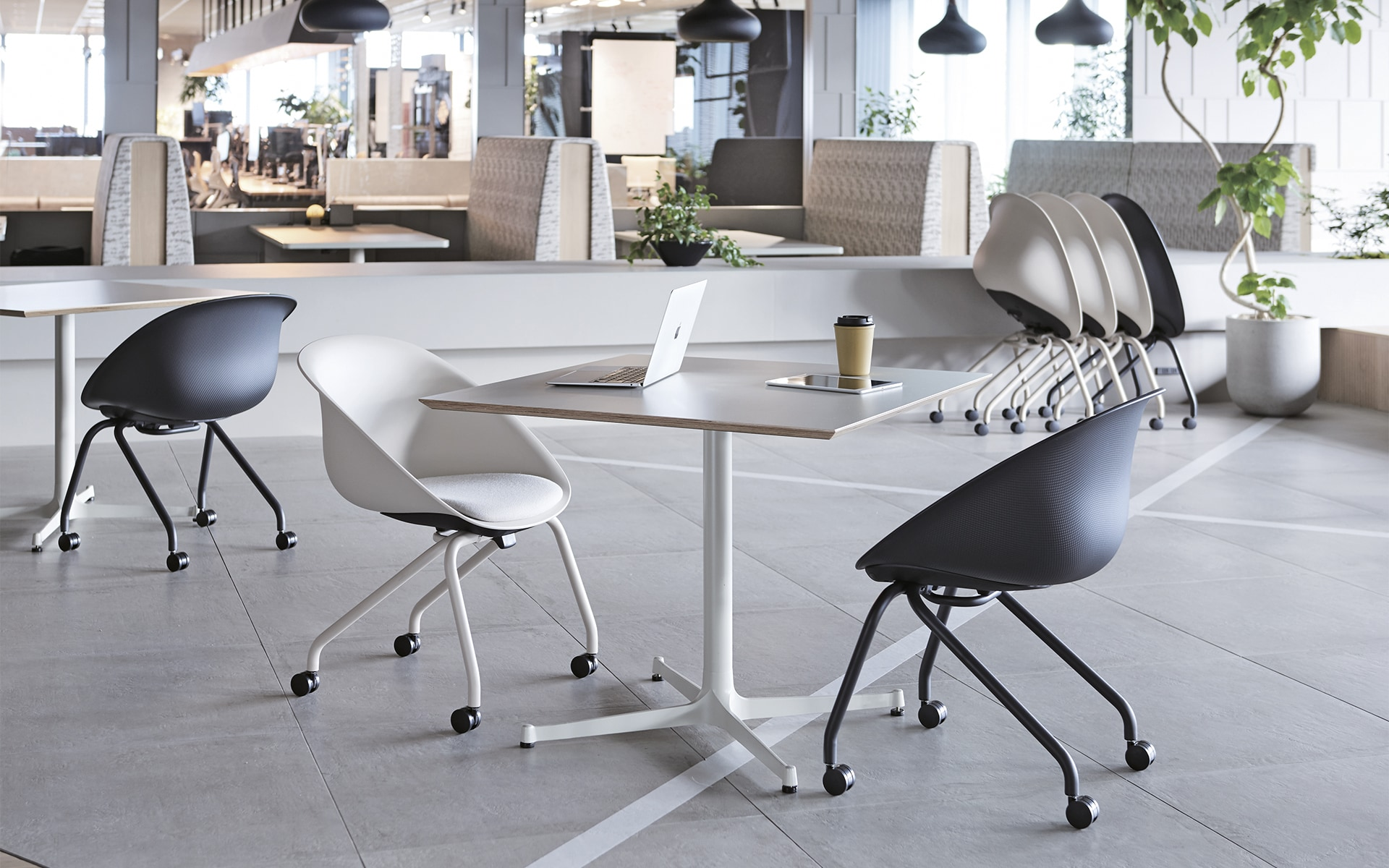 Several ITOKI Wan shell chairs by ITO Design in black and white in modern co-working space