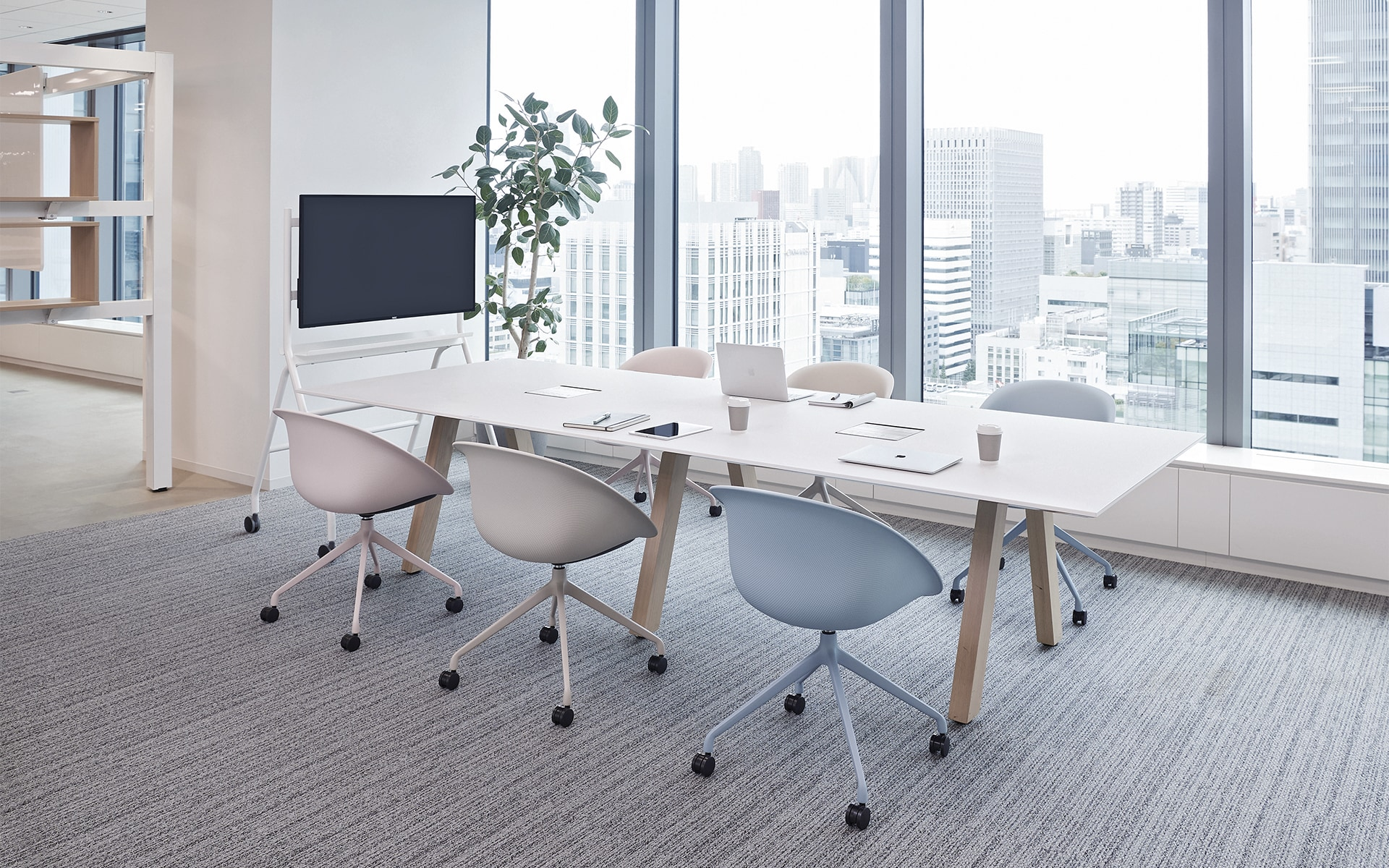 A bright conference room with six ITOKI Wan shell chairs by ITO Design in pale pink, white and pastel blue