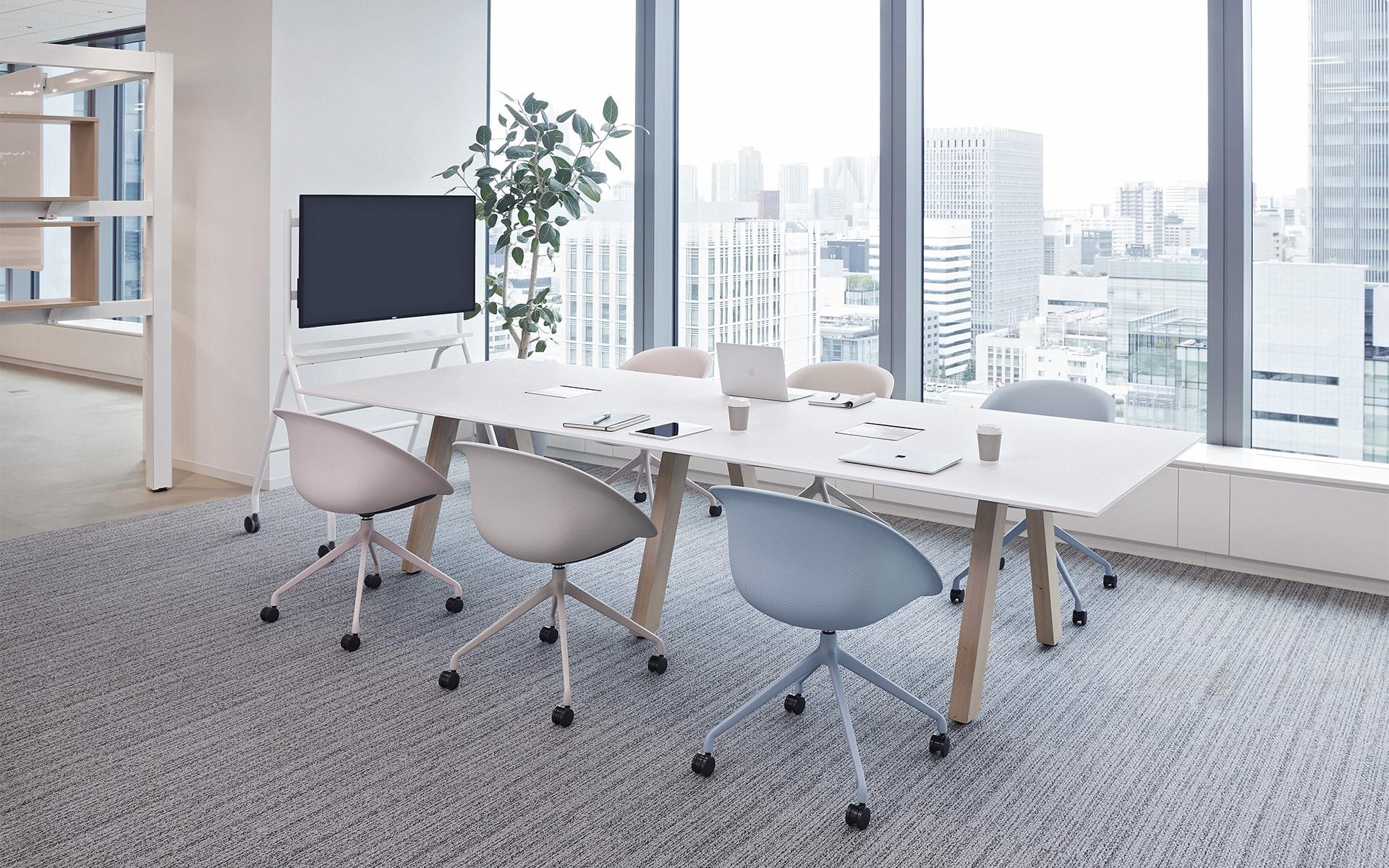 Ein lichtdurchfluteter Konferenzraum mit sechs ITOKI Wan Schalenstühlen von ITO Design in hellrosa, weiß und pastellblau