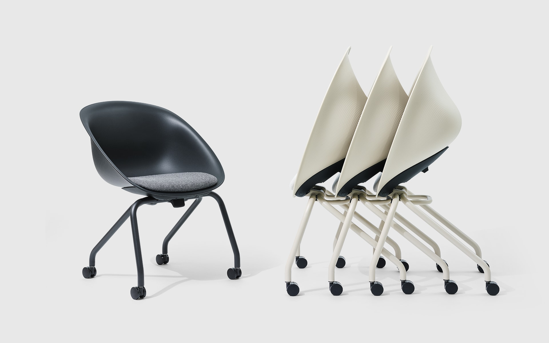 One black and three white, nested ITOKI Wan shell chairs by ITO Design