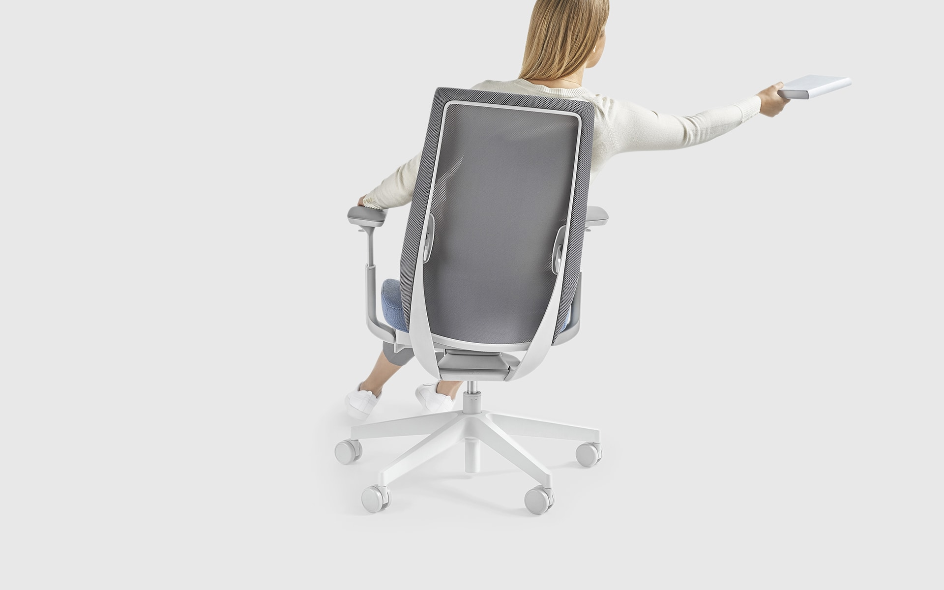 A woman sitting actively in a light grey Profim Accis Pro office chair by ITO Design