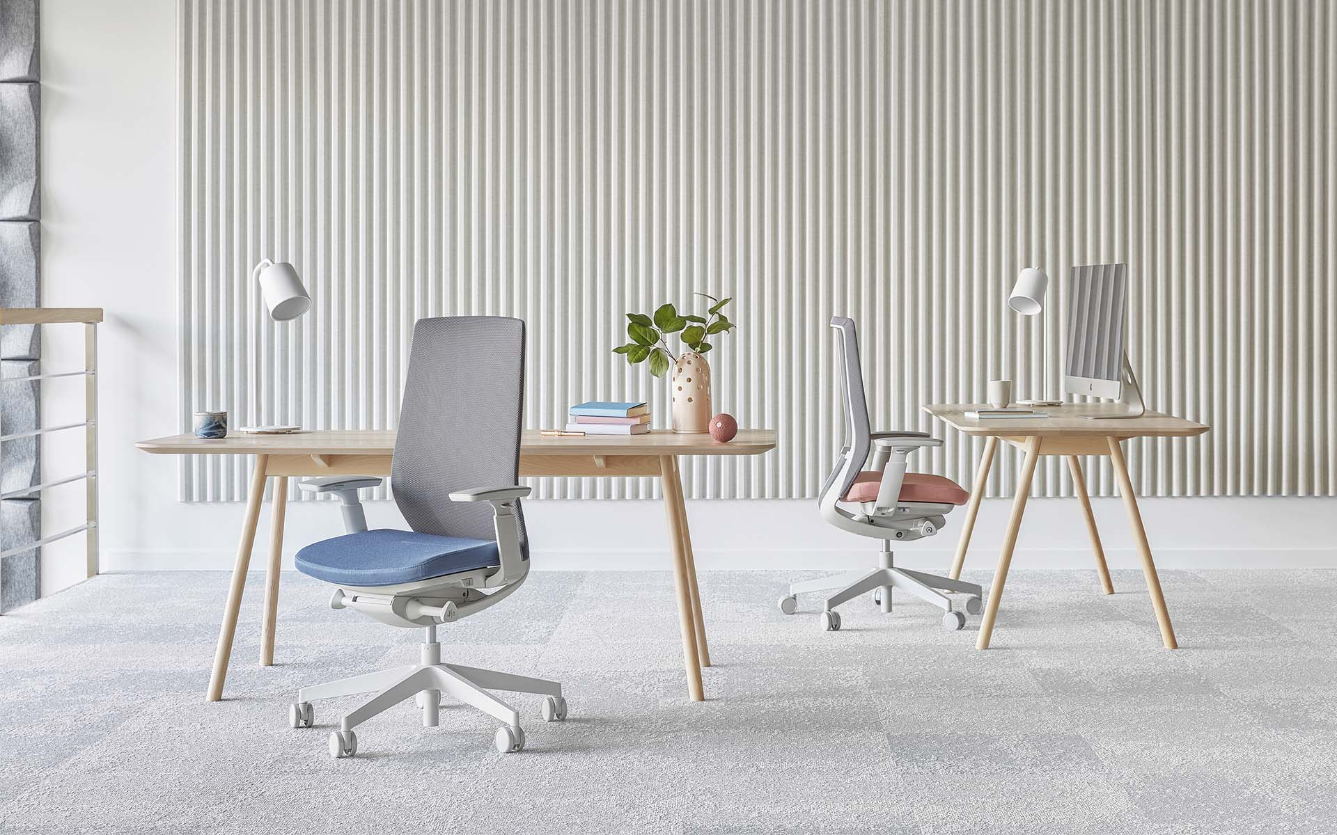 Two Profim Accis Pro office chairs by ITO Design with light blue and pink upholstery in minimalist office