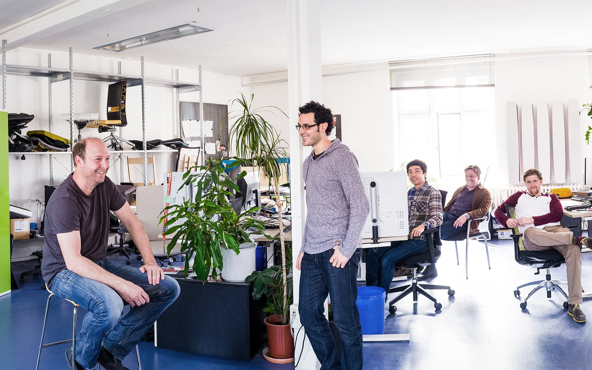 Five ITO Design colleagues in the open space office, in the background prototypes of office chairs