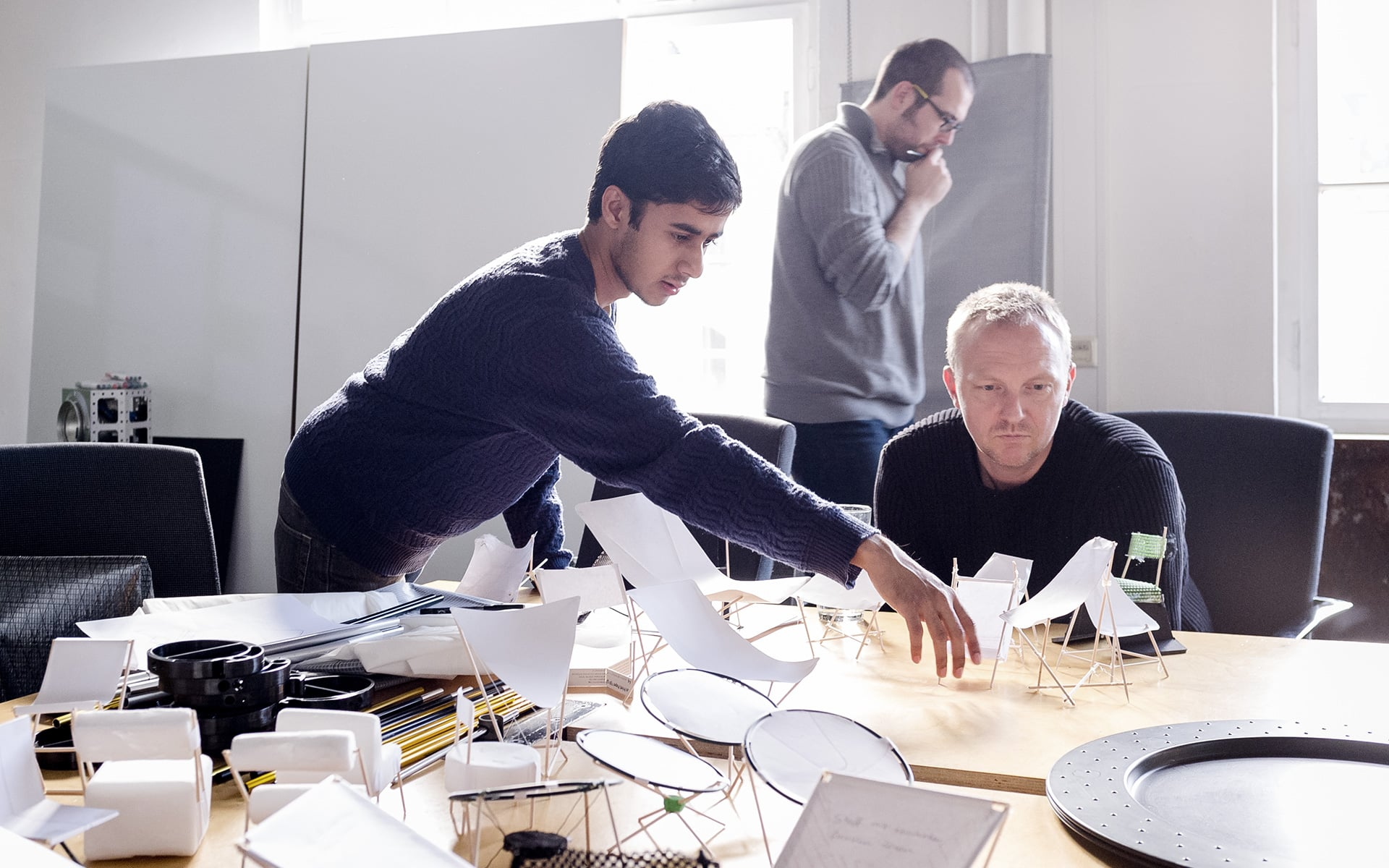 ITO Design colleagues arrange several small models of a chair design