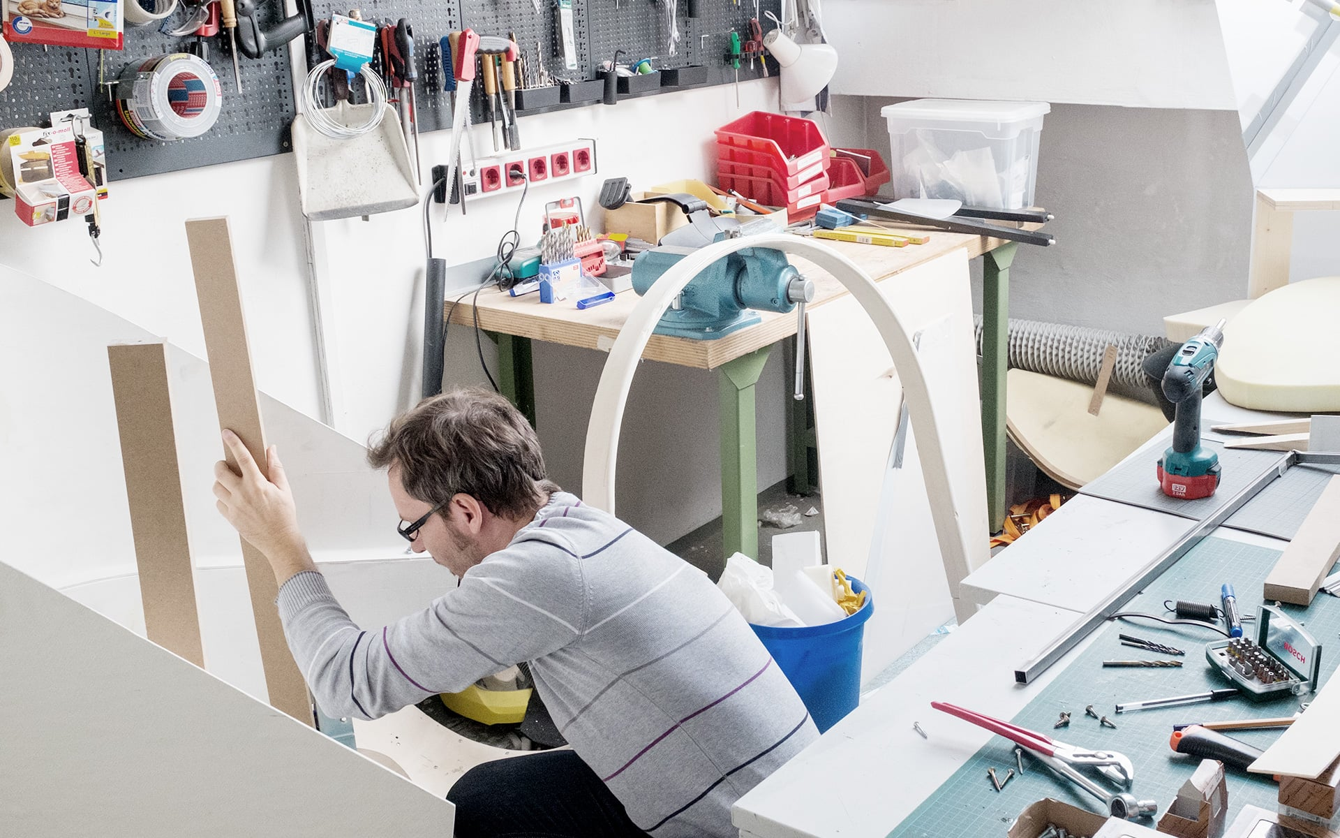 An ITO Design colleague builds a chair prototype at a workbench