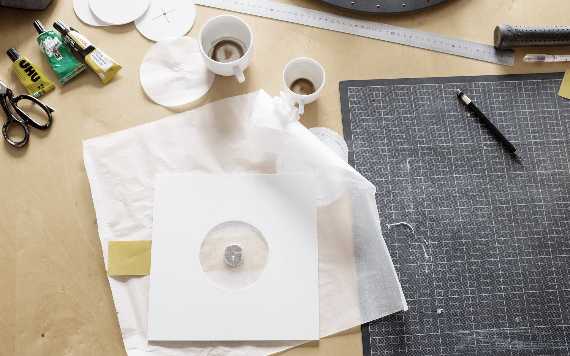 Work surface with mold for magnet disk, working utensils and empty coffee cups at ITO Design